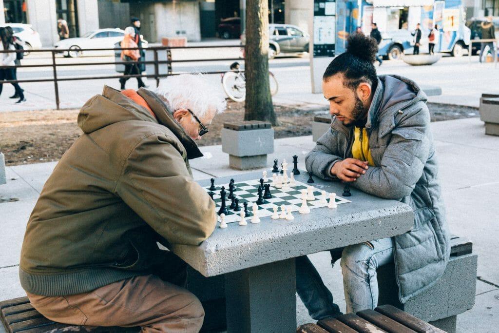 Twee mannen aan het schaken, 1 jong, 1 oud
